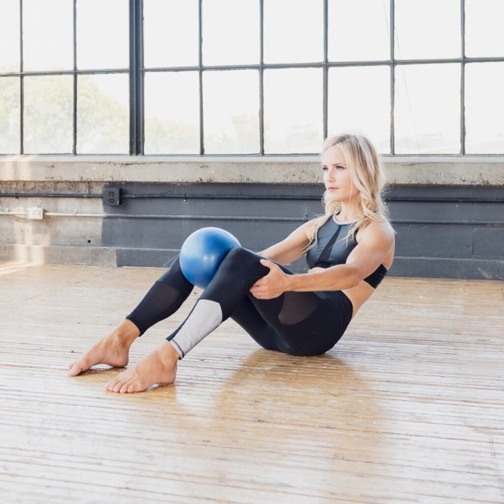 Natalya in a brightly lit pilates loft studio using a small squishy balance ball between her knees